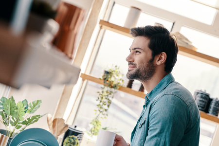 Nice morning. Handsome young man in casual wear drinking coffee and smiling while standing in the kitchen at home