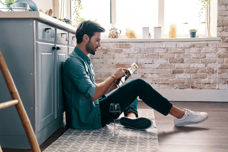 Just surfing the net. Handsome young man in casual wear using digital tablet and drinking wine while sitting on the kitchen floor
