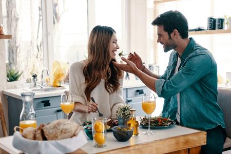 ¡Prueba esto! Hermosa joven pareja disfrutando de un desayuno saludable mientras está sentado en la cocina de casa Foto de archivo