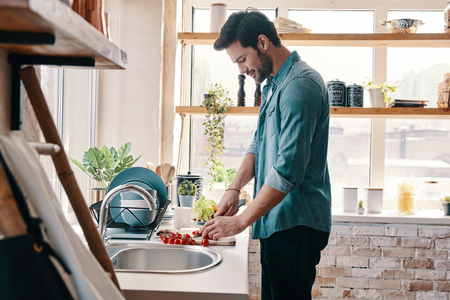 Time to have breakfast. Handsome young man in casual wear chopping food and smiling while standing in the kitchen at home Imagens
