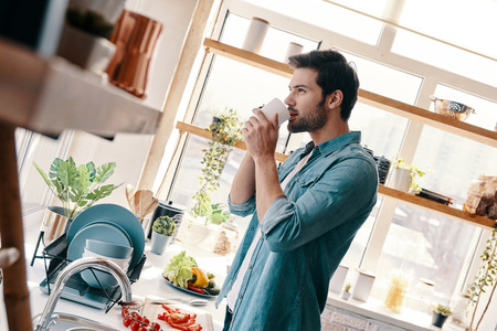 Enjoying morning coffee. Handsome young man in casual wear drinking coffee and smiling while standing in the kitchen at home 스톡 콘텐츠