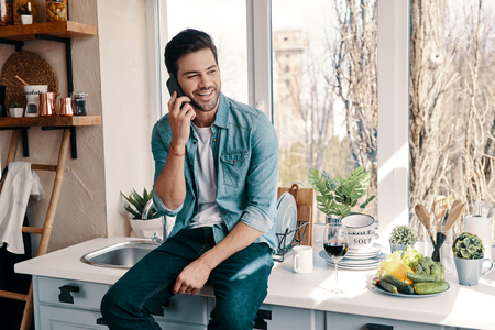 Happy talk. Handsome young man in casual wear talking on the phone while sitting in the kitchen at home 스톡 콘텐츠