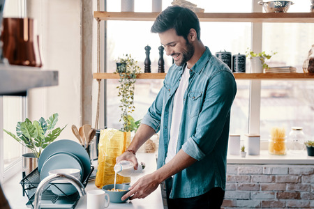 ust add some milk. Handsome young man in casual wear preparing corn flakes and smiling while standing in the kitchen at home