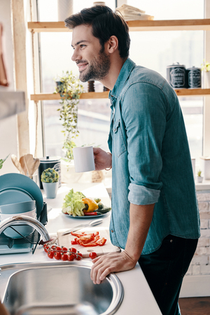 Morning filled with joy. Handsome young man in casual wear drinking coffee and smiling while standing in the kitchen at home