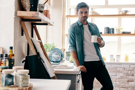 Morning coffee. Handsome young man in casual wear looking at camera and having a hot drink while standing in the kitchen at home 스톡 콘텐츠