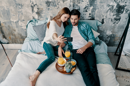 Let me take a selfie! Top view of beautiful young couple taking selfie and smiling while spending time in bed at home