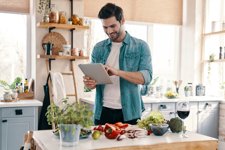 Following recipe. Handsome young man in casual wear using digital tablet and smiling while standing in the kitchen at home