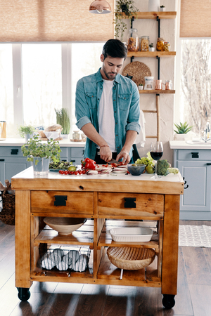 Modern manhood. Handsome young man in casual wear cutting vegetables while standing in the kitchen at home