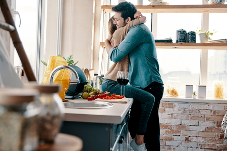 Love is more than just a game for two. Beautiful young couple cooking dinner and drinking wine while standing in the kitchen at home