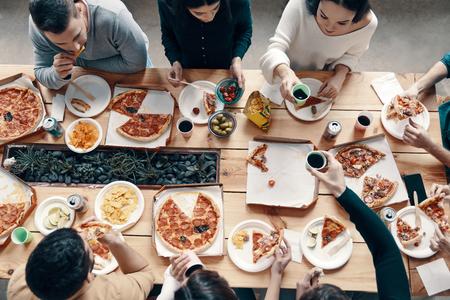La migliore cena. Vista dall'alto di giovani in abbigliamento casual che raccolgono la pizza mentre fanno una cena al chiuso Archivio Fotografico