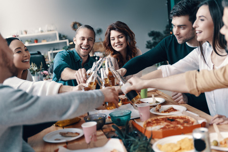 So much fun together! Group of young people in casual wear toasting each other and smiling while having a dinner party indoors