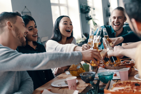 Friendship that lasts forever. Group of young people in casual wear toasting each other and smiling while having a dinner party indoors Banco de Imagens