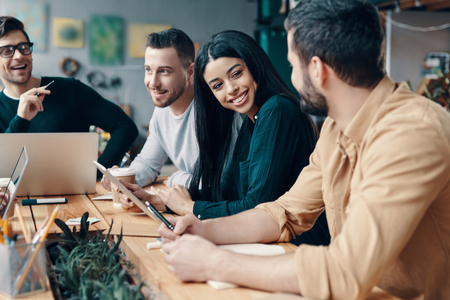Business is not boring. Group of young modern people in smart casual wear discussing something and smiling while working in the creative office Stock Photo