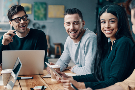 Happy coworkers. Group of young modern people in smart casual wear discussing something and smiling while working in the creative office Stock Photo