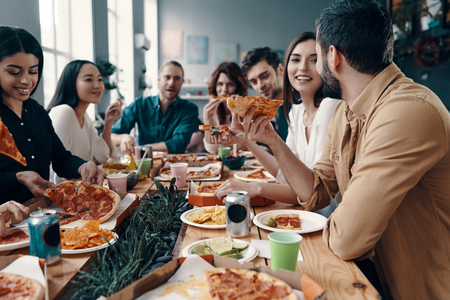 Holiday among friends. Group of young people in casual wear eating pizza and smiling while having a dinner party indoors