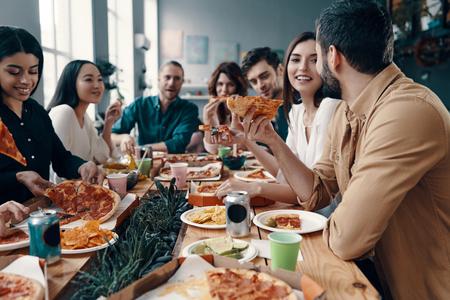 Urlaub unter Freunden. Gruppe junger Leute in Freizeitkleidung, die Pizza isst und lächelt, während sie eine Dinnerparty im Haus veranstalten