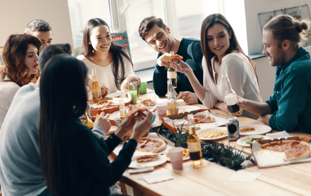 Unforgettable party. Group of young people in casual wear eating pizza and smiling while having a dinner party indoors Stok Fotoğraf