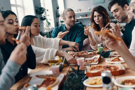 Dzielenie się wspaniałym posiłkiem. Grupa młodych ludzi w strojach codziennych jedzących pizzę i uśmiechających się podczas kolacji w pomieszczeniu