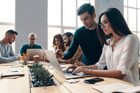 Team working together. Group of young modern people in smart casual wear using modern technologies while working in the creative office Imagens