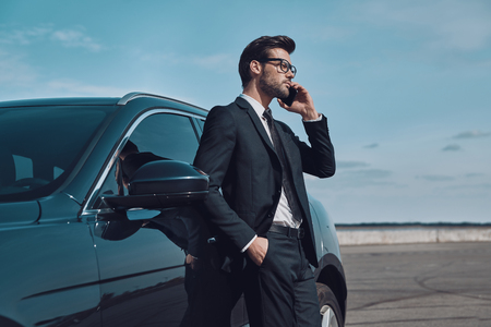 Always available. Handsome young businessman talking on the phone while standing near his car outdoors