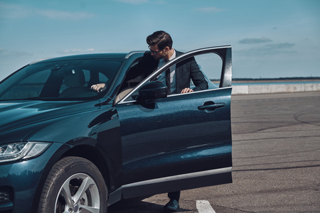 Brand new car. Handsome young businessman entering his car while standing outdoors