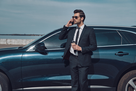 Time is money. Handsome young businessman talking on his smart phone and smiling while standing near his car outdoors