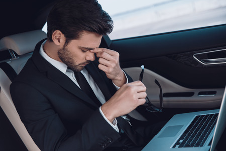 So tired! Top view of frustrated young man in full suit massaging nose while sitting in the car Stok Fotoğraf