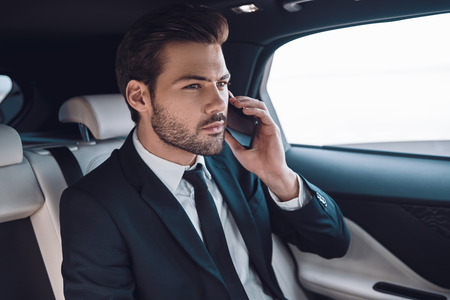 Taking everything seriously. Handsome young man in full suit talking on the smart phone while sitting in the car Stok Fotoğraf