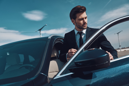 Business travel. Handsome young man in business wear entering his car while standing outdoors