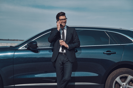 I am waiting for you! Handsome young businessman talking on his smart phone and smiling while standing near his car outdoors Stock Photo