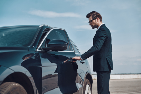 Status car owner. Handsome young businessman entering his car while standing outdoors Фото со стока