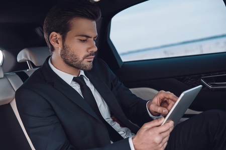 Concentrated at work. Handsome young man in full suit working using digital tablet while sitting in the car