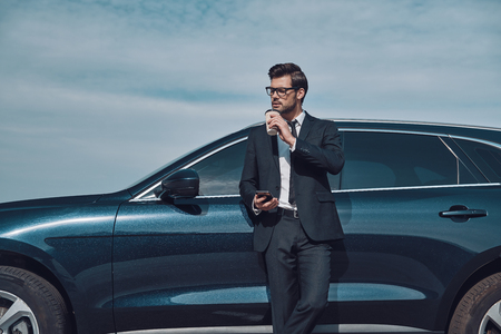 Moment to relax. Handsome young businessman using smart phone and drinking coffee while standing near his car outdoors