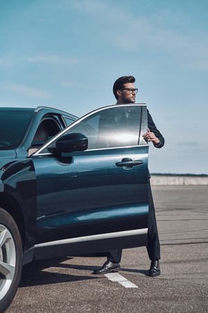 Ready to go. Handsome young businessman entering his car and looking away