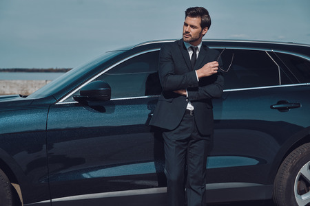 Thinking about... Handsome young businessman keeping arms crossed and smiling while standing near his car outdoors