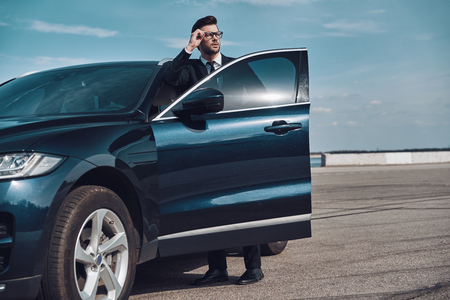 Elegant businessman. Handsome young businessman entering his car while standing outdoors