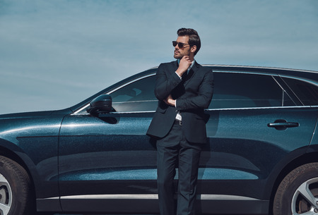 Confidence and charisma. Handsome young businessman keeping hand on chin while standing near his car outdoors
