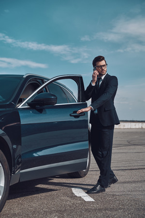 I will be in time! Full length of handsome young businessman talking on the phone while entering his car outdoors Stok Fotoğraf