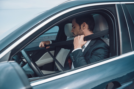 Safety comes first. Handsome young man in full suit applying seat belt while driving a car 写真素材