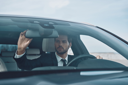 Checking every detail. Handsome young man in full suit adjusting rear-view mirror while driving a car