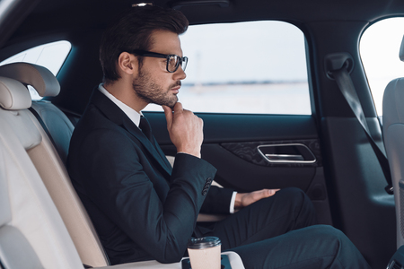 Thinking about solution. Thoughtful young man in full suit keeping hand on chin while sitting in the car