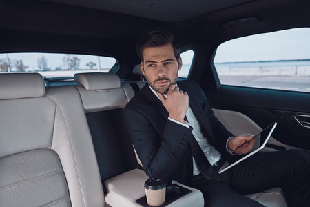 Young perfectionist. Handsome young man in full suit working using digital tablet while sitting in the car Stok Fotoğraf - 122384014