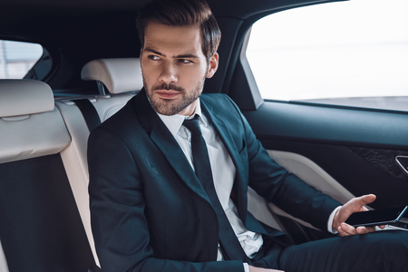 Young and successful. Handsome young man in full suit looking away while sitting in the car