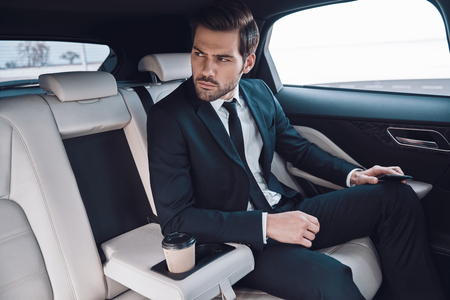 Confident businessman. Handsome young man in full suit looking away while sitting in the car Stok Fotoğraf - 122384017