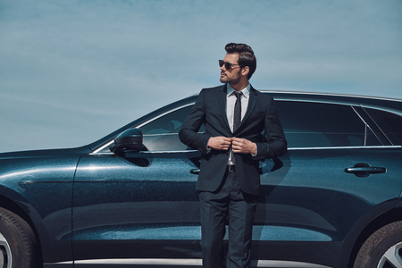 Always on style. Handsome young businessman adjusting jacket and smiling while standing near his car outdoors