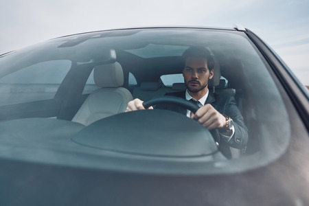 Busy day. Handsome young man in full suit looking straight while driving a car