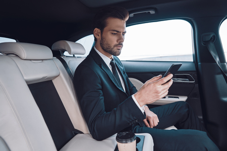 Young perfectionist. Handsome young man in full suit using his smart phone while sitting in the car