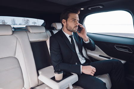 Business on the move. Handsome young man in full suit talking on the smart phone while sitting in the car