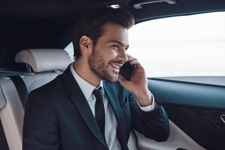 Good talk. Handsome young man in full suit talking on the smart phone and smiling while sitting in the car