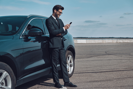 Confident manager. Full length of handsome young businessman using smart phone while standing near his car outdoors Stok Fotoğraf